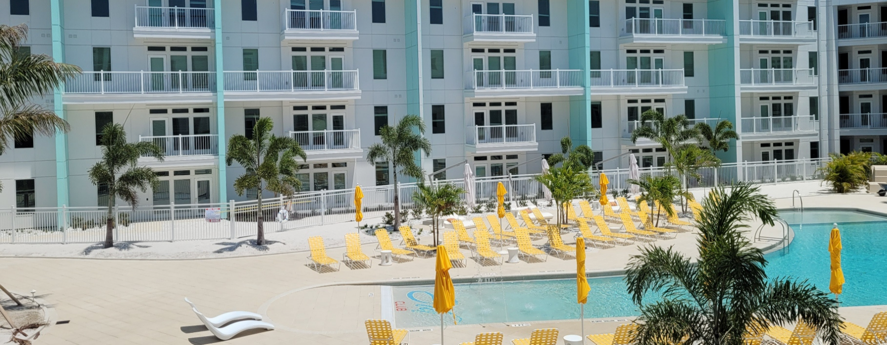 exterior of apartment building with pool deck and pool furniture