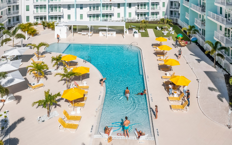 aerial view of pool and deck with yellow umbrellas